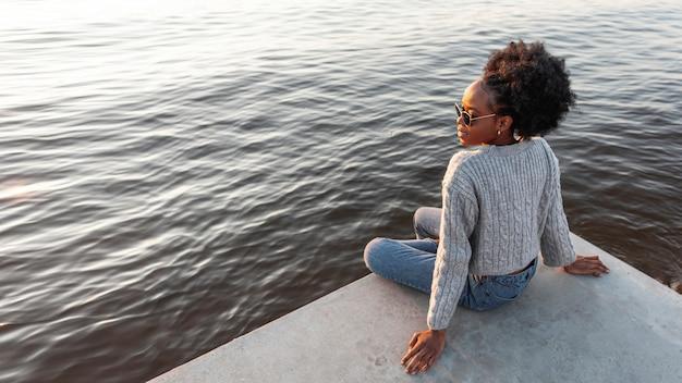 Donna africana di vista posteriore che si siede vicino all'acqua