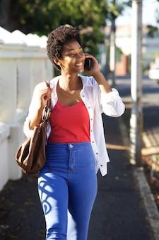 Donna africana felice che parla sul telefono cellulare