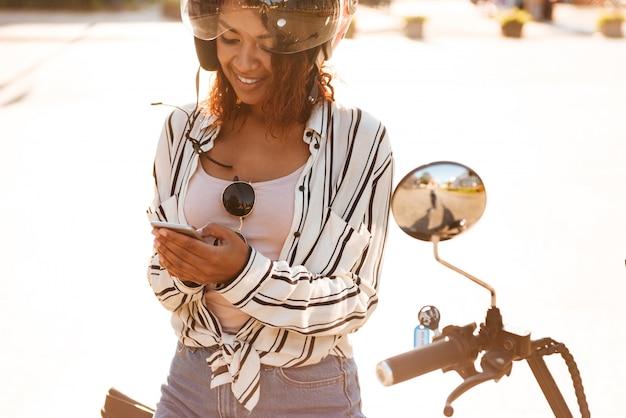 Donna africana sorridente che si siede sulla motocicletta moderna all'aperto e che per mezzo del suo smartphone