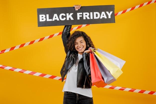 Donna africana sorridente con il segno di venerdì nero e sacchetti della spesa variopinti isolati sopra giallo con nastro adesivo