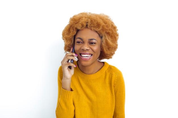 Donna africana sorridente dei giovani che parla sul telefono.