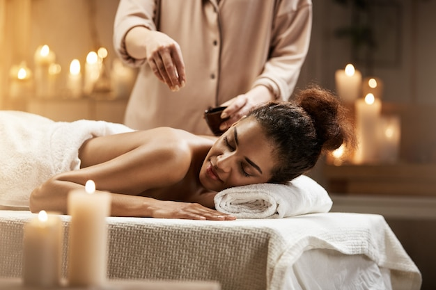 Donna africana tenera che si rilassa godendo del massaggio sano della stazione termale con olio.
