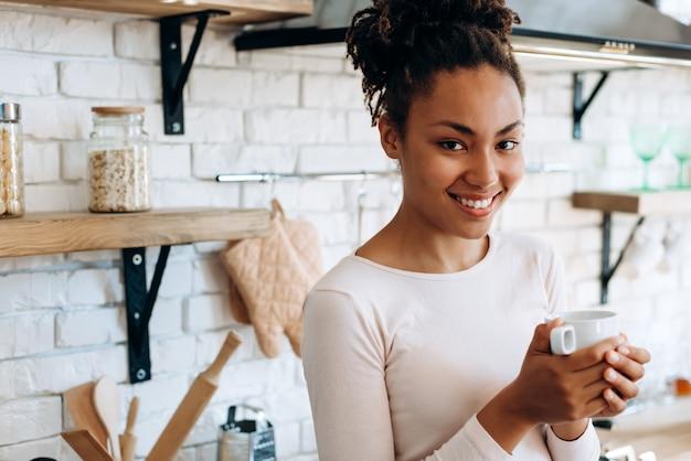 Donna afro-americana con un caffè in cucina