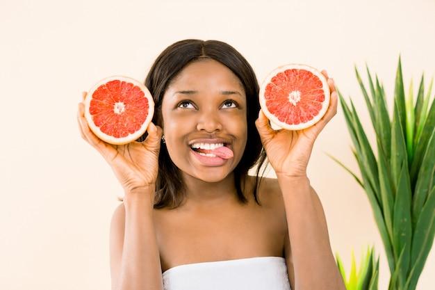Donna afro-americana con un pompelmo su uno sfondo bianco, mostrando la sua lingua. cura della pelle bellezza.