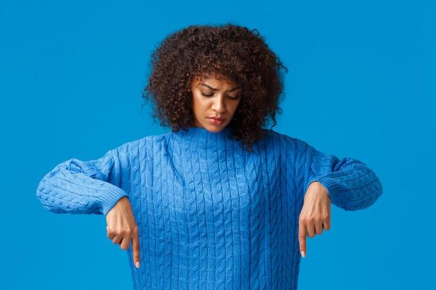 Donna afro-americana turbata e cupa dall'aspetto serio con taglio di capelli afro che ha vacanze invernali tristi, guardando e indicando le dita verso il basso, fissando delusa, in piedi sfondo blu