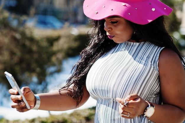Donna afroamericana al cappello che cammina sulle strade con il telefono sulle mani.
