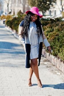 Donna afroamericana al cappello e cappotto con il telefono che cammina alle strade.