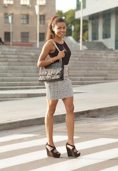 Donna afroamericana alla moda che cammina sull'attraversamento o sul passaggio pedonale.