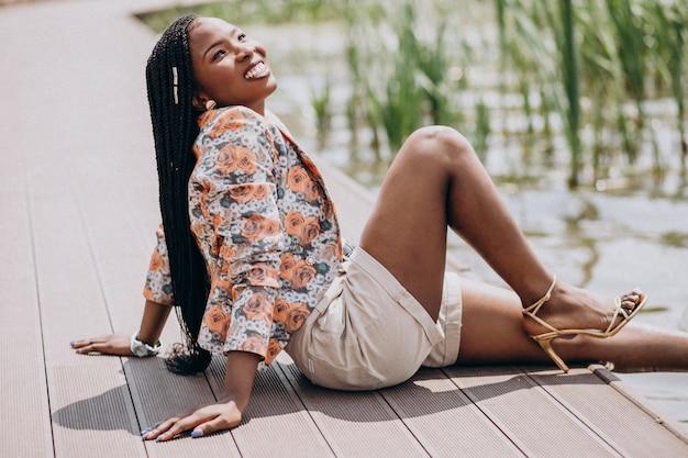 Donna afroamericana alla moda che si siede sul lago nel parco