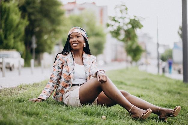 Donna afroamericana alla moda nel parco che si siede sull'erba