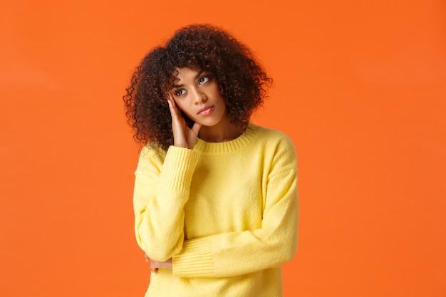 Donna afroamericana annoiata disinteressata in maglione giallo, viso, distogliendo lo sguardo con espressione disinteressata e scettica, partecipa a una festa noiosa, in piedi arrabbiata e insoddisfatta dell'arancia