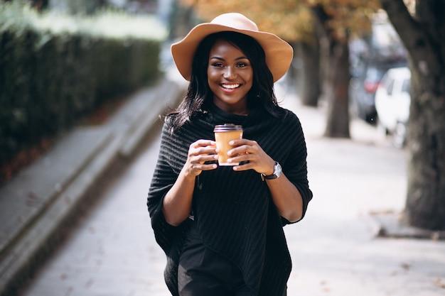 Donna afroamericana bere caffè e parlando al telefono