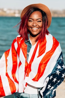 Donna afroamericana che avvolge nella bandiera degli stati uniti