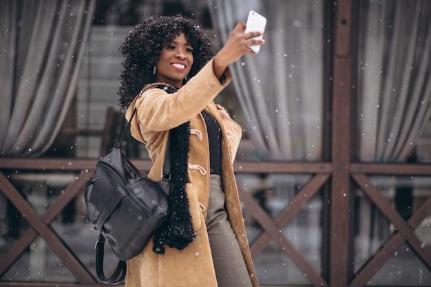 Donna afroamericana che fa selfie in inverno