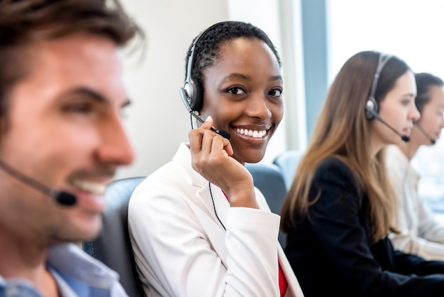 Donna afroamericana che lavora nell'ufficio di call center con squadra diversificata