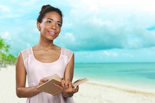 Donna afroamericana che legge un libro di romanzo sulla spiaggia, vacanze estive