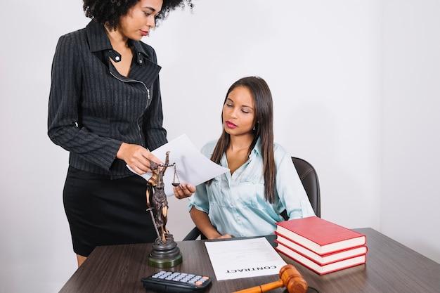 Donna afroamericana che mostra documento alla signora alla tavola con i libri, il calcolatore e la figura