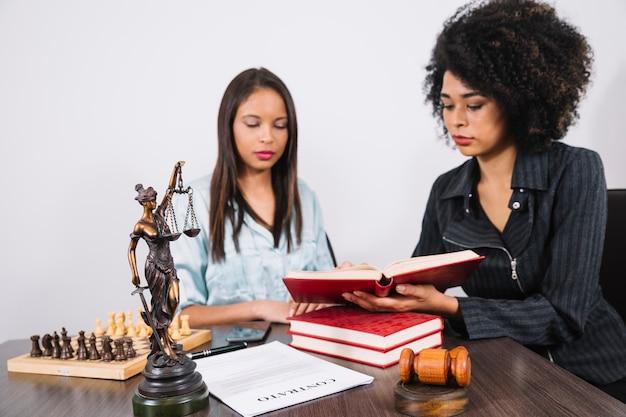 Donna afroamericana che mostra libro a signora al tavolo con documento, smartphone e scacchi