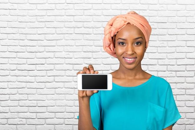 Donna afroamericana che mostra un telefono cellulare