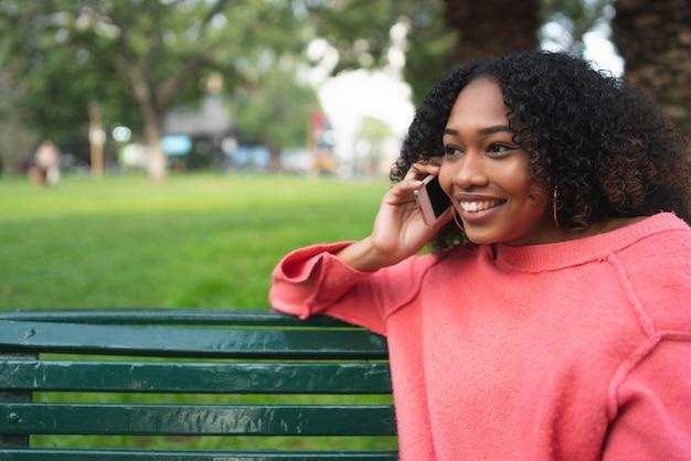 Donna afroamericana che parla sul telefono.