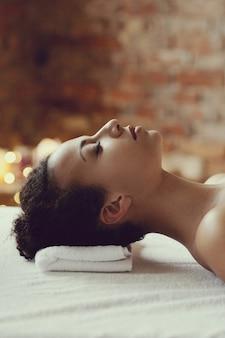 Donna afroamericana che riceve un massaggio rilassante presso la spa