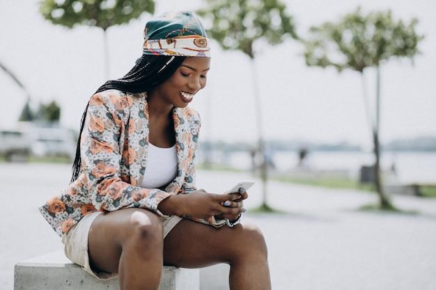 Donna afroamericana che si siede nel parco e che per mezzo del telefono