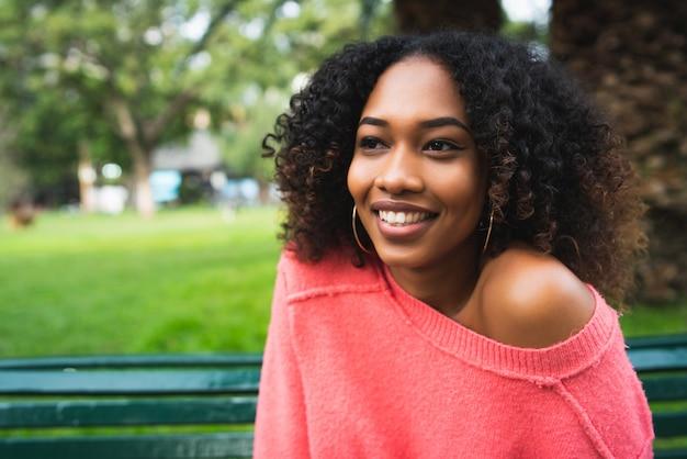 Donna afroamericana che si siede nel parco.