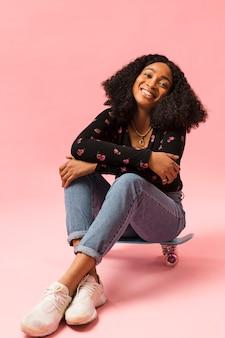Donna afroamericana che si siede sullo skateboard