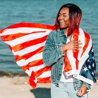 Donna afroamericana che sta con la bandiera americana sulla spalla