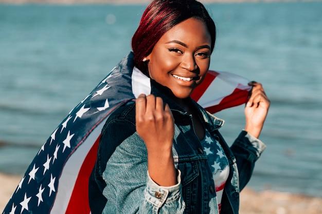 Donna afroamericana che tiene la bandiera americana alle spalle