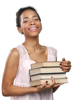 Donna afroamericana che tiene una pila di libri