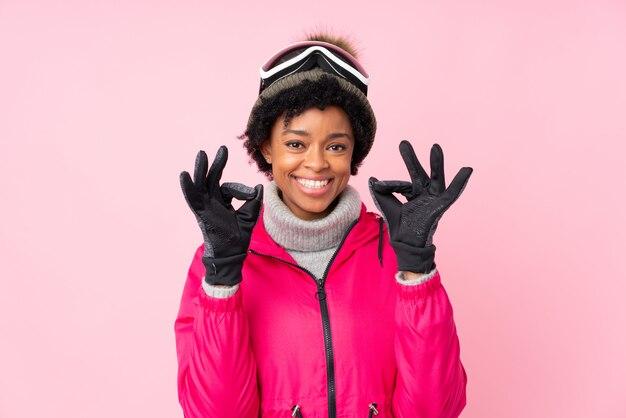 Donna afroamericana con i vetri di sci sopra la parete rosa isolata