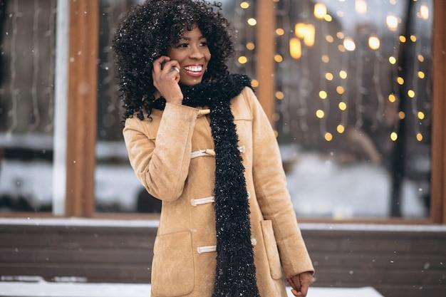 Donna afroamericana con il telefono in inverno