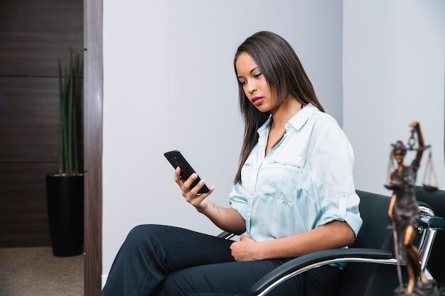 Donna afroamericana con lo smartphone che si siede sulla poltrona in ufficio