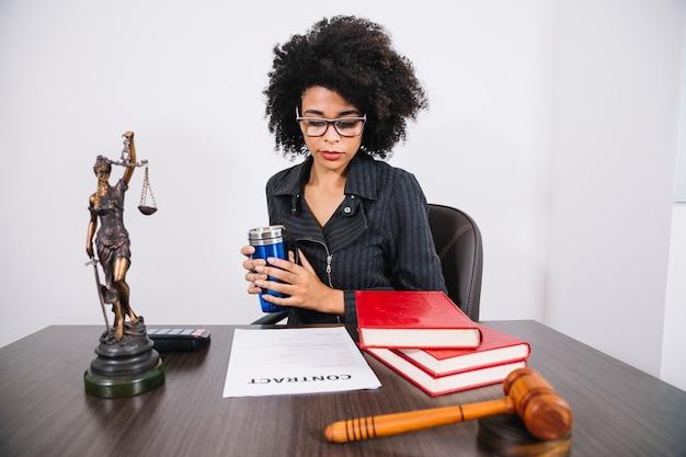 Donna afroamericana con thermos al tavolo vicino a calcolatrice, libri, documenti e statue