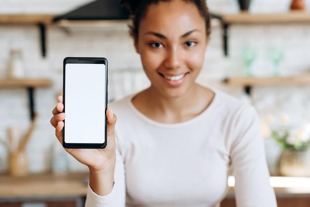 Donna afroamericana con un telefono in cucina