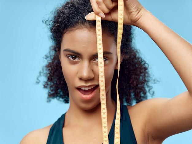 Donna afroamericana dalla carnagione scura che posa in una tuta sportiva e che fa lo spazio di sport