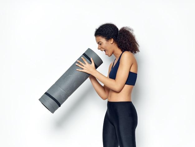 Donna afroamericana dalla pelle scura che posa in una tuta sportiva e che fa sport