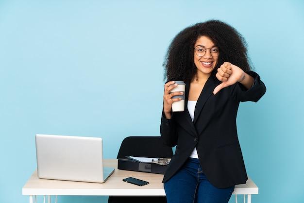 Donna afroamericana di affari che lavora nel suo posto di lavoro che mostra pollice giù