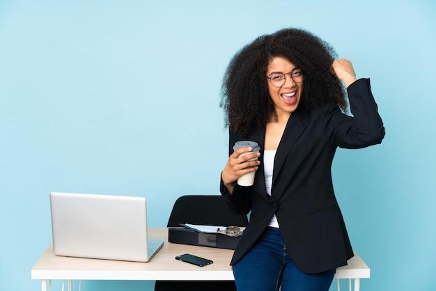Donna afroamericana di affari che lavora nel suo posto di lavoro facendo un gesto forte