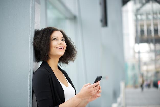 Donna afroamericana di affari che sorride con il telefono cellulare
