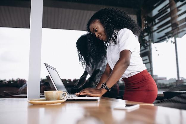 Donna afroamericana di affari con il computer e telefono in un caffè