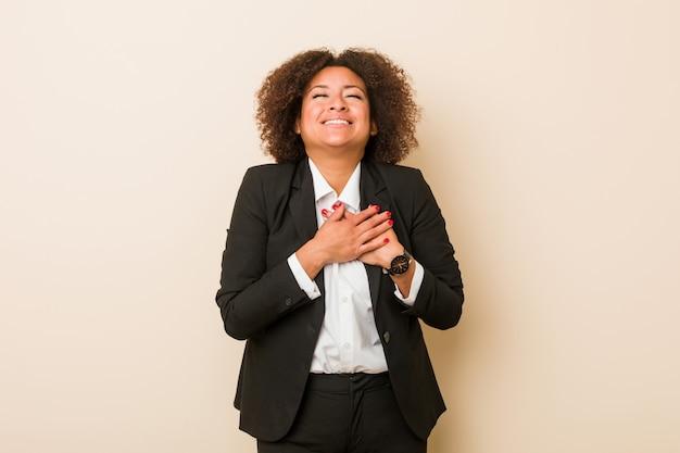 Donna afroamericana di giovani affari che ride tenendo le mani sul cuore, concetto di felicità.