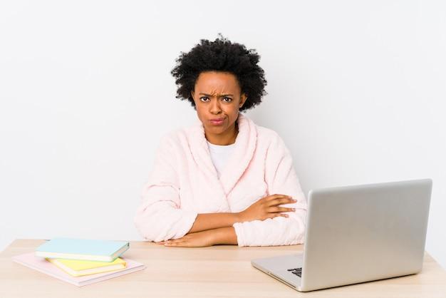 Donna afroamericana di mezza età che lavora a casa infelice guardando in camera con l'espressione sarcastica.