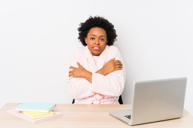 Donna afroamericana di mezza età che lavora a casa isolata andando a freddo a causa della bassa temperatura o di una malattia.