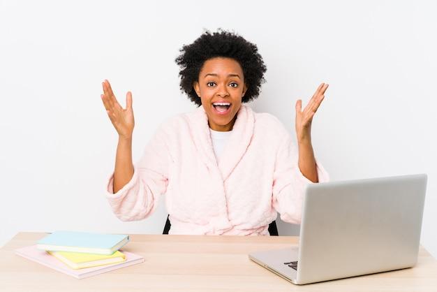 Donna afroamericana di mezza età che lavora a casa ricevendo una piacevole sorpresa, eccitata e alzando le mani.