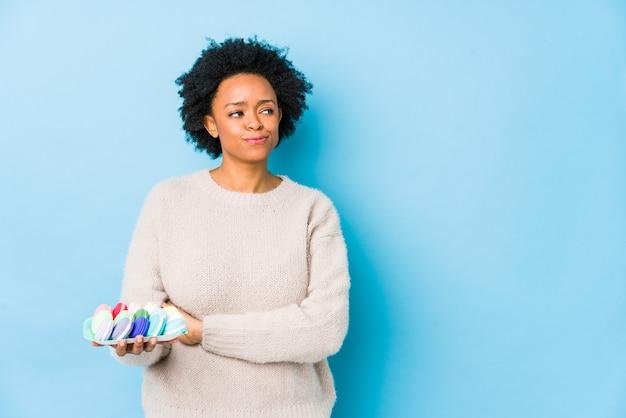 Donna afroamericana di mezza età che mangia amaretti isolato sorridente fiducioso con le braccia incrociate.