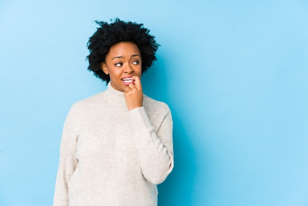 Donna afroamericana di mezza età contro un muro blu isolato rilassato pensando a qualcosa guardando uno spazio di copia.