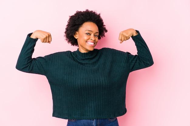 Donna afroamericana di mezza età contro un muro rosa isolato mostrando il gesto di forza con le braccia, simbolo del potere femminile