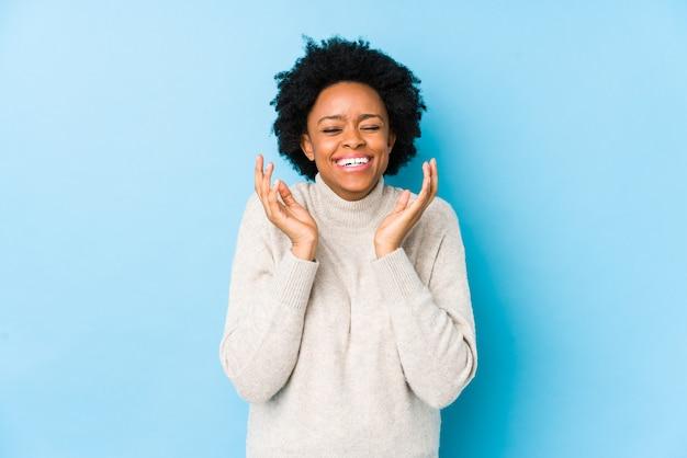 Donna afroamericana di mezza età contro uno sfondo blu isolato gioiosa ridendo molto. concetto di felicità.